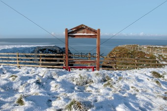 seasonal snow covered framed red bench sea view