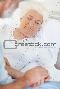 Caring senior man with a sick mature woman lying in bed