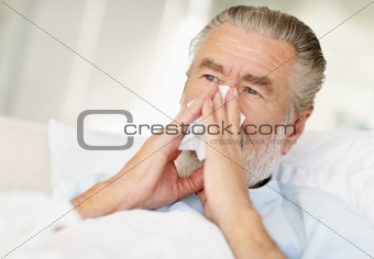 Closeup of a sick senior man blowing his nose into a tissue