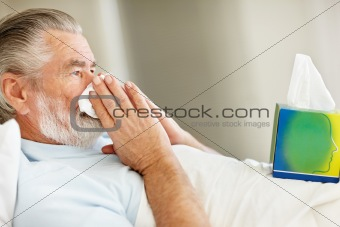 Senior man suffering from cold blowing his nose into a tissue