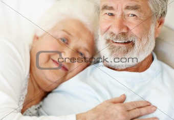 Relaxed senior couple lying together on bed