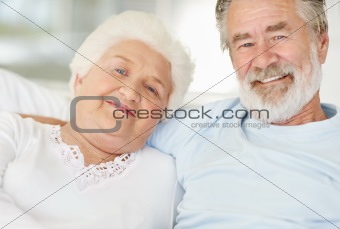 Happy senior couple sitting together at home