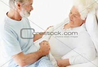 Caring mature man comforting a sick senior woman