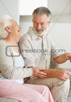 Joyful mature female with a smiling senior man holding a laptop