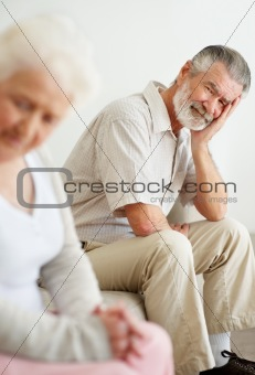 Depressed mature man looking at a sad senior woman