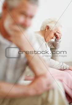 Stressed mature couple sitting on sofa after a quarrel