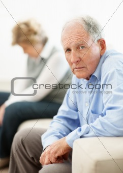 Sad mature man sitting on sofa with a woman after a quarrel