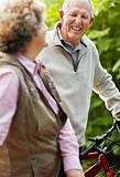 Happy mature man with senior woman riding bicycle in countryside