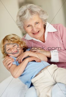 Playful child sitting on his grandmothers lap