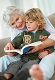 Small boy and grandmother reading book while sitting in couch
