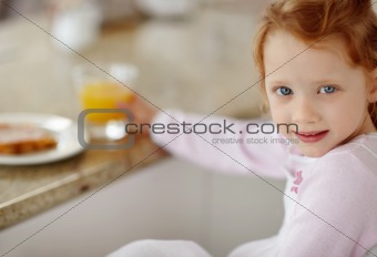 Happy girl holding a glass of juice while having breakfast