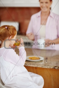 Small girl drinking juice while senior woman in blur background