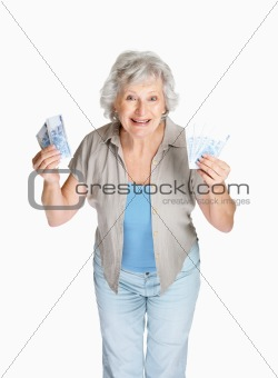 Happy senior woman holding cash in hands on white background