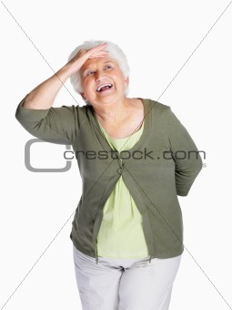 Happy senior woman shielding her eyes isolated against white