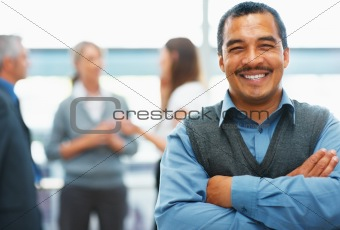 Happy businessman with supportive team in background