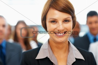 Smiling female executive with colleagues in background