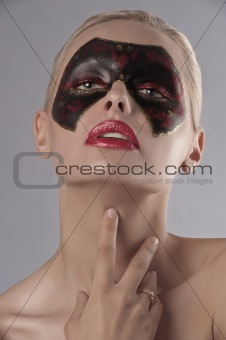 blonde model posing with a painted mask on her face
