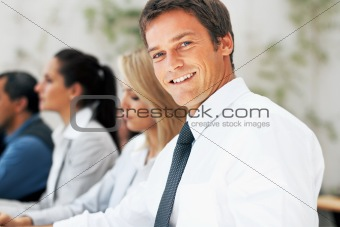 Businessman in meeting with colleagues in background