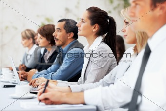 Executives listening and writing notes during meeting