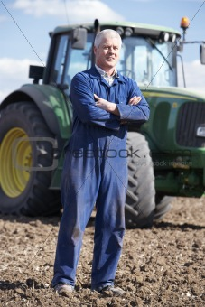 Driver Standing In Front Of Tractor