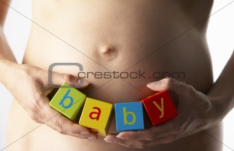 "Pregnant Woman Holding Blocks Spelling ""Baby"""