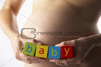 """Pregnant Woman Holding Blocks Spelling """"Baby"""""""