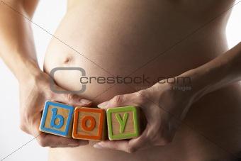 "Pregnant Woman Holding Blocks Spelling ""Boy"""