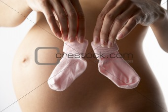Pregnant Woman Holding Pink Baby Socks
