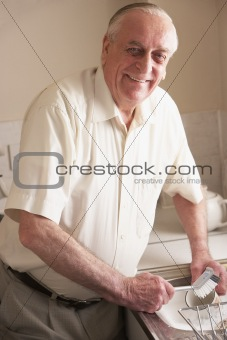 Senior Man Washing Up At Sink
