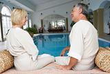 Middle Aged Couple Relaxing By Swimming Pool