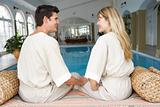 Young Couple Relaxing By Swimming Pool