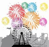 fireworks and silhouettes of a city and amusement park