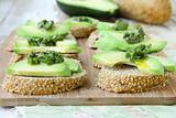 Sandwich with pesto sauce and avocado on a wooden board