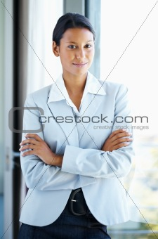 Female executive standing casually with arms folded