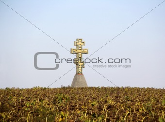 Autumn landscape with sunflower and cross