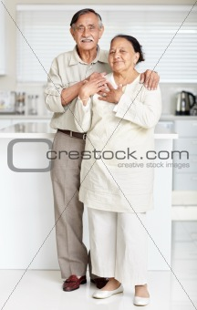 Happy old couple standing together in a kitchen