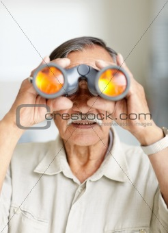 Portrait of a old man looking through binoculars