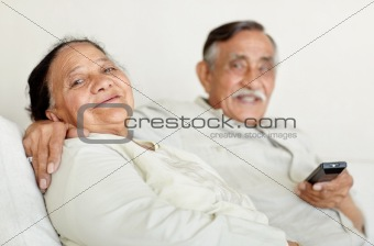 Cute senior couple watching televison together