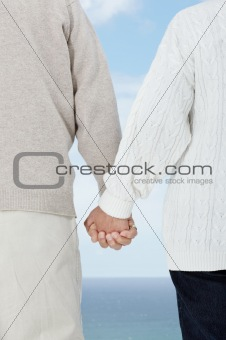 Old couple walking hand in hand against the sky
