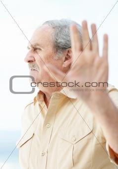 An angry mature man showing stop sign