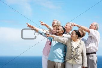 A  group of old people pointing at copyspace - Outdoor