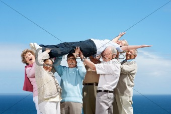 Enjoyment - Group of old friends lifting a woman up