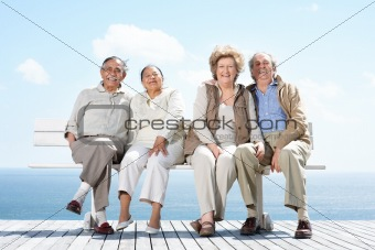Happy senior couples sitting together on the bench