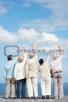 Group of old friends pointing upwards at the sky