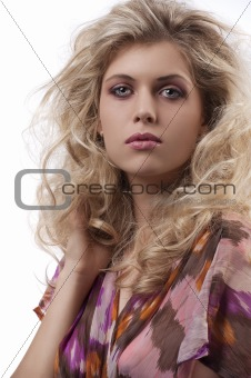 beautiful woman with long curly blond hair looking at the camera
