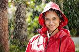Happy young teenage girl in a red raincoat smiling