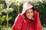 Excited young female holding a red raincoat hat on head