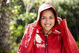 Beautiful young girl in red raincoats enjoying the rain