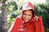 Pretty young woman holding a raincoat hat on head