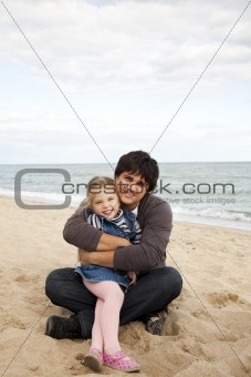 Father and daughter at the beach in fall.